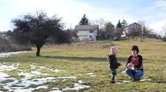 Stock Video Footage of Mother and little child kid play with last snow on nature meadow
