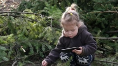 Little kid girl play smart phone app outdoors in forest park nature - stock footage