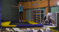 Jumping on trampoline. Young woman. fun Stock Footage