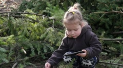 Little kid girl play smart phone app outdoors in forest park nature Stock Footage
