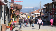 Tourists and store hotel buildings of ski resort Bansko in Bulgaria Stock Footage