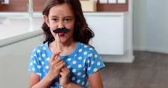 Cute child with fake mustaches making faces - stock footage