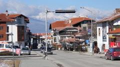 Street traffic and store hotel buildings of ski resort Bansko in Bulgaria Stock Footage