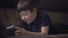 boy relaxing on sofa watching using playing games digital tablet surfing the net - stock footage