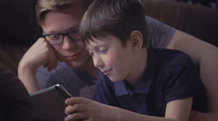 Brothers relaxing on sofa playing digital tablet surfing the net Stock Footage