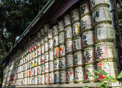 Japanese Barrels of Sake wrapped in Straw stacked on shelf Stock Photos