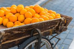 Fresh oranges on vintage wooden cart - stock photo