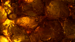 Cola soft drink bubbles & ice, close-up Stock Footage