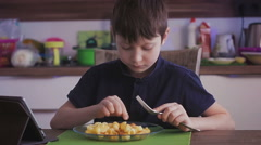adorable child having meal eating macaroni chicken watching digital tablet - stock footage