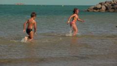 happy kids running around on the beach - stock footage