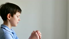 Boy teenager praying belief in god Stock Footage