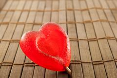 Stock Photo of Valentine day concept - heart shaped lolly pop on wood background