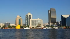 Large inflatable yellow rubber duck on Dubai Creek water, city buildings on back Stock Footage