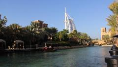 Water taxi, small abra boat move along waterway at Madinat Jumeirah Stock Footage