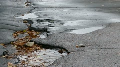 bad  asphalt rain tarmac pits in pool floating leaves are fallin - stock footage