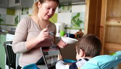 BABY slide his finger across the touch screen Samsung Taplet PC while feeding - stock footage