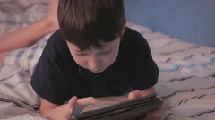 Little boy relaxing on his bed playing digital tablet ipad computer games Stock Footage