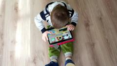 Top view of a baby playing with a big tablet PC games on Android Stock Footage