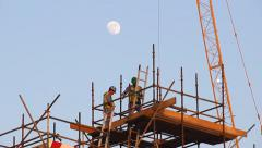 Top of scaffolds, worker climb down ladder, dusk time, telephoto lens - stock footage