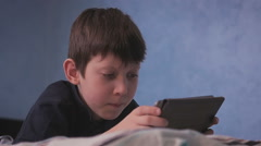 little boy relaxing on his bed playing digital tablet ipad computer games - stock footage
