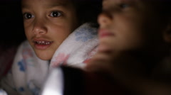4K Two children under a blanket reading a bedtime story at night with a torch Stock Footage