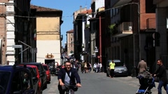 People walk and ride bicycles by the street in Rimini, Italy. Stock Footage