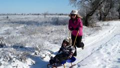 Mother and son sledding on a snowy winter road Stock Footage