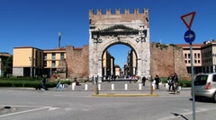 People walk in front of the Arch of Augustus in Rimini, Italy. Stock Footage