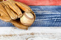 Close up of old worn baseball mitt and baseball on faded wooden boards painte - stock photo
