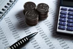 Money in the form of banknotes and coins with calculator Stock Photos