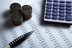 money in the form of banknotes and coins with calculator - stock photo