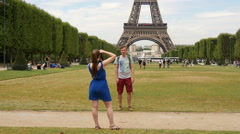 Young couple taking pictures with the Eiffel Tower in background, Paris Stock Footage