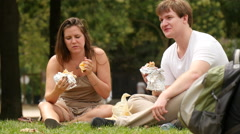 Young couple sitting and eating in a park, Paris Stock Footage