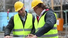 Construction site manager explaining blueprints - stock footage