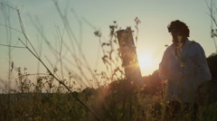 Old artist paints a picture in the field at sunset Stock Footage