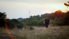 Owner and german shepherd walking in the fields on the sunset Stock Footage
