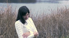Woman girl cold rubs his hands in white jacket from grass dry Stock Footage
