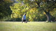 Young german shepherd and trainer walking in the field side wide Stock Footage