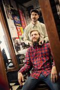 Stock Photo of Male barber checking symmetry beard.