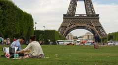 Stock Video Footage of Couple sitting on grass and taking pictures in the Champ de Mars, Paris