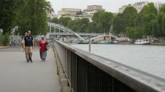 People walking on the river bank close to Passarelle Debilly in Paris Stock Footage