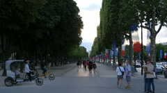 People walking, couple hugging and tricycles parked on a street in Paris Stock Footage