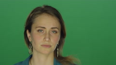 woman looking annoyed and glaring, on a green screen background - stock footage