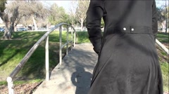 Backside of Old Woman Walking With Cane In City Park Stock Footage