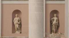People walking near statues of women on Palazzo della Borsa Vecchia in Trieste Stock Footage