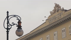 Vintage lamp post and sculptures on top of Palazzo Tregesteo in Trieste Stock Footage