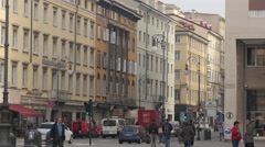 People walking and cars driving on the street of Piazza della Borsa in Trieste Stock Footage