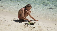 Yuong girl playing with toy ship on the beach Stock Footage