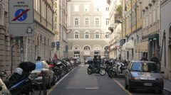 Man parking his  motor scooter on Via di Torre Bianca in Trieste Stock Footage