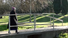 Old Grandma Walking with Cane On Park Bridge - stock footage